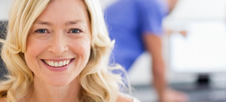 Patientin mit breitem Lächeln, wegen günstigem Zahnersatz