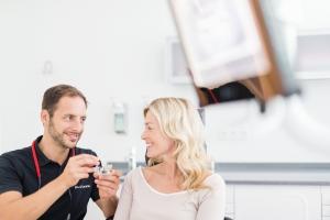 Zahnarzt im Bespräch mit Patientin über gesundes Zahnfleisch