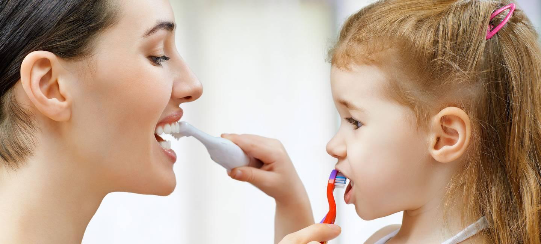 Mutter und Kind putzen gegenseitig ihre Zähne